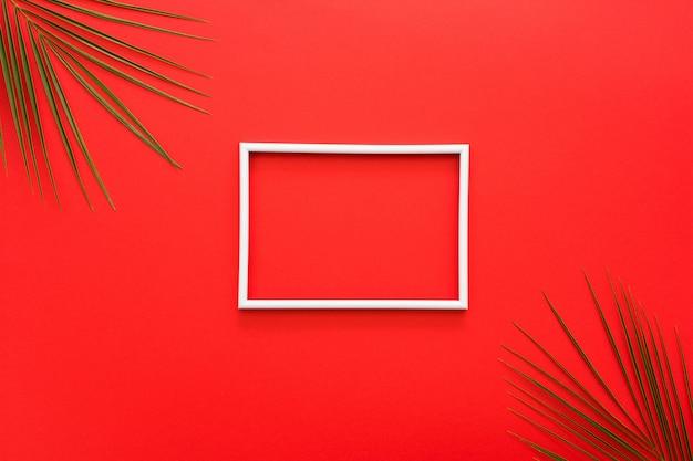 Weißer rand des feldes und der palmblätter auf roter oberfläche Kostenlose Fotos