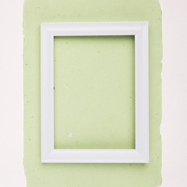 Weißer rechteckiger grenzrahmen auf tadellosem grünbuch auf weißem hintergrund Kostenlose Fotos