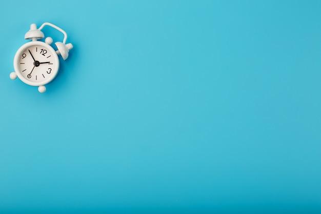 Weißer retro-wecker auf blauer oberfläche Premium Fotos