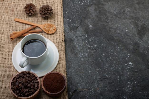 Weißer schalenkaffee, kaffeebohnen in der hölzernen schale, kiefer auf leinwand auf dem schwarzen gemaserten stein Premium Fotos