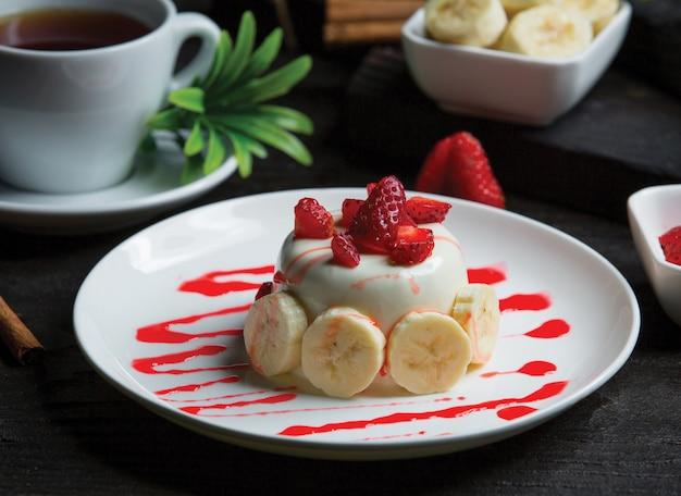 Weißer schokoladenkleiner kuchen mit bananen und erdbeeren Kostenlose Fotos