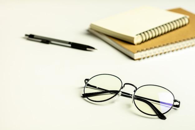 Weißer schreibtisch mit gläsern, stift und einem leeren notizbuch. Premium Fotos