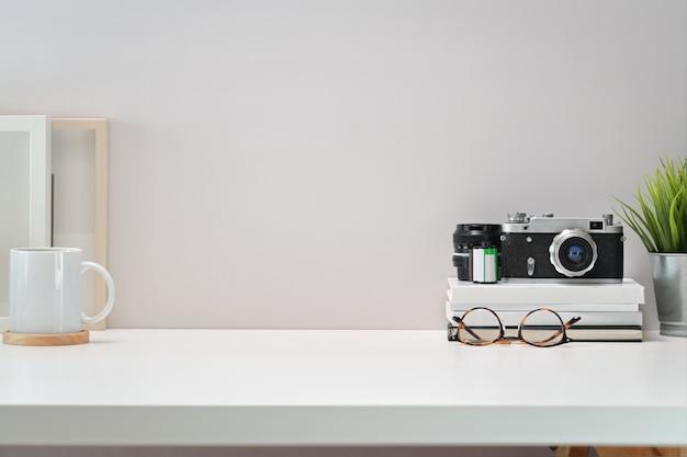 Weißer skandinavischer arbeitsplatzschreibtisch mit weinlesekamera, filmen, plakat und kopienraum Premium Fotos