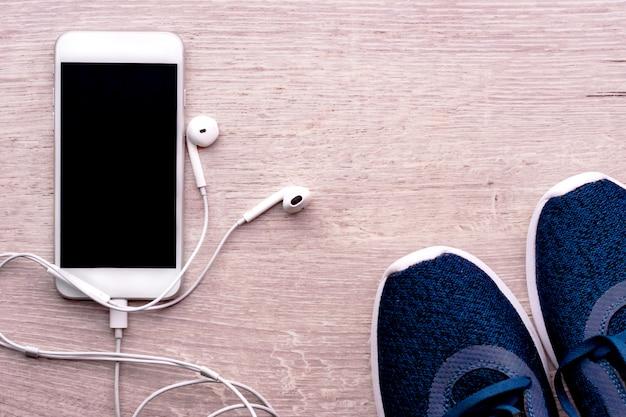 Weißer smartphone mit den kopfhörern angeschlossen, nahe bei sportschuhen. gesundes lebensstilkonzept, eignung. Premium Fotos