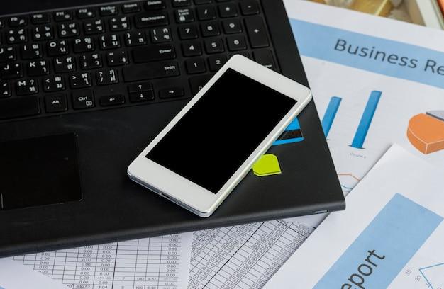 Weißer smartphone mit schwarzem freiem raum auf notizbuch nahe geschäftsdiagrammbericht geschäftskonzept. Premium Fotos