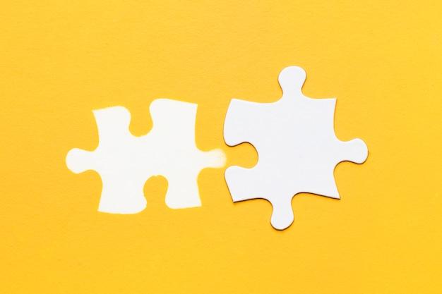Weißer stempel des puzzlespielstückes mit papppuzzlespielstück auf gelber oberfläche Kostenlose Fotos