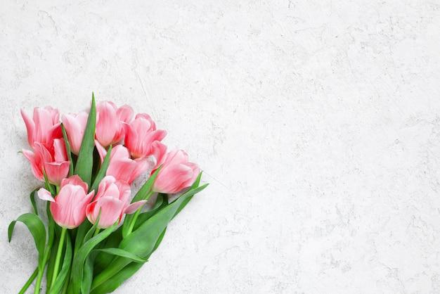 Weißer strukturierter hintergrund mit frischen zarten tulpen Premium Fotos
