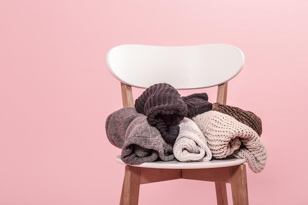 Weißer stuhl mit einem stapel gestrickter pullover an einer rosa wand Kostenlose Fotos