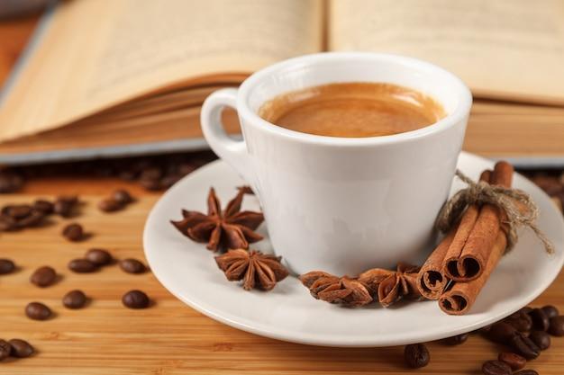 Weißer tasse kaffee-espresso, umgeben von gerösteten kaffeebohnen Premium Fotos