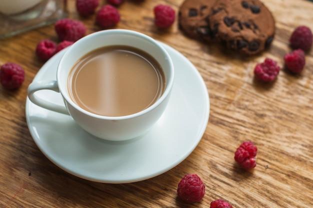 Weißer tasse kaffee mit schokoladenplätzchen und -himbeeren auf hölzernem hintergrund Kostenlose Fotos