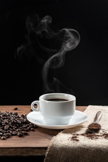 Weißer tasse kaffee und kaffeebohnen liefen de-beutel über Premium Fotos