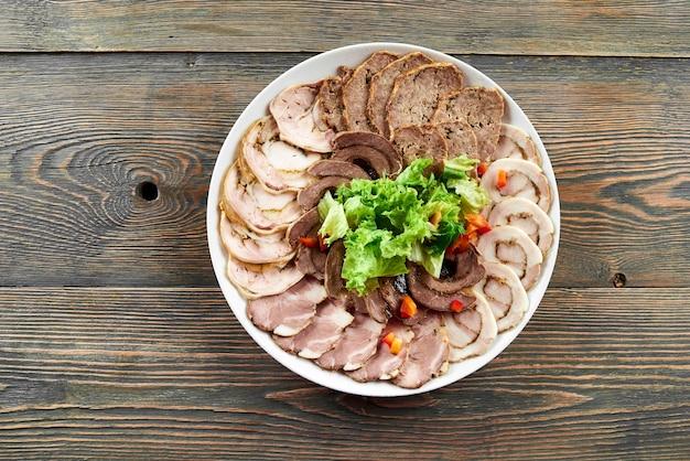 Weißer teller auf einem holztisch voller gefüllter fleischscheibensortiment Premium Fotos