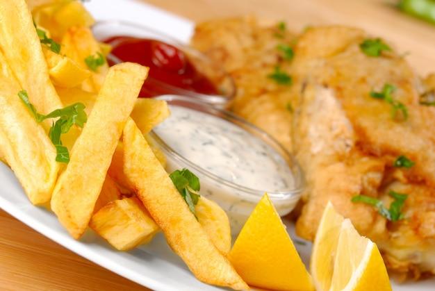 Weißer teller mit fisch, pommes, mayo, ketchup und zitrone Premium Fotos