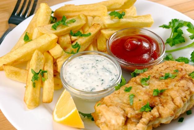 Weißer teller mit fish and chips, mayo, zitrone und ketchup Premium Fotos
