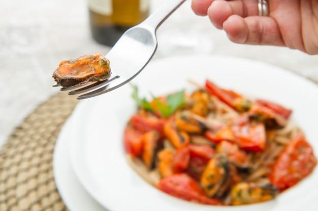 Weißer teller mit teigwarenspaghettis, -muschel und -tomaten Premium Fotos