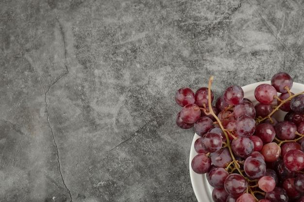 Weißer teller und rote köstliche trauben auf marmortisch. Kostenlose Fotos