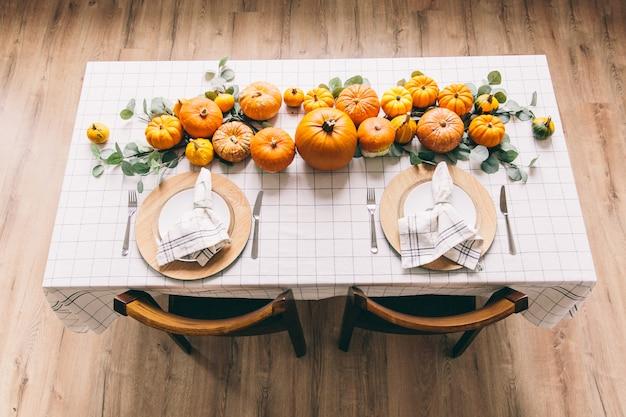 Weißer tisch mit geschirr und speisen im zimmer. gelbe kürbise auf dem tisch im café. Premium Fotos