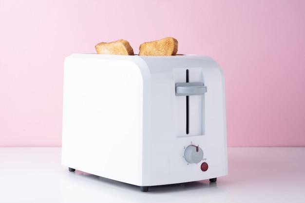 Weißer toaster mit gebratenem toastbrot auf rosa hintergrund, abschluss oben Premium Fotos