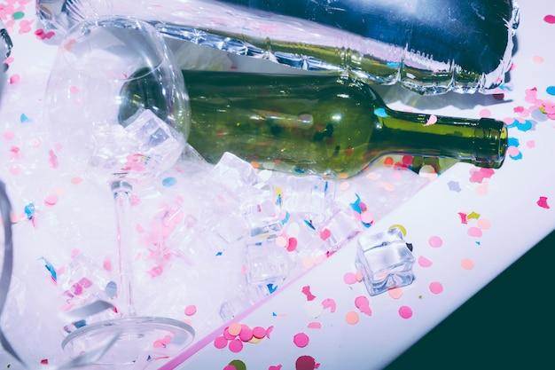 Weißer unordentlicher tisch mit leerem weinglas; grüne alkoholflasche; eiswürfel und konfetti nach der geburtstagsfeier Kostenlose Fotos