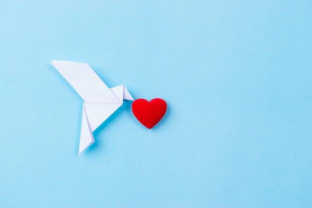 Weißer vogel gemacht vom papier, das rotes herz trägt. internationaler tag des friedens. Premium Fotos