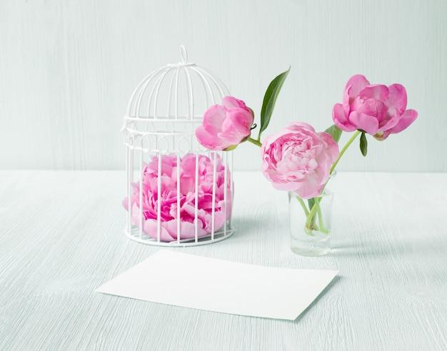 Weißer vogelkäfig mit blütenblättern auf holztisch. drei pfingstrosenblüten in glasvase. leere einladungskarte für hochzeitsfeier. Kostenlose Fotos
