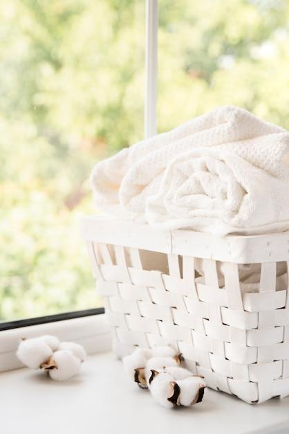 Weißer wäschekorb neben einem fenster Kostenlose Fotos