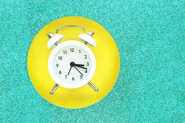 Weißer wecker, der in ein rundes loch in einer glänzenden türkispappe auf einem gelben hintergrund fällt. platz für text. Premium Fotos