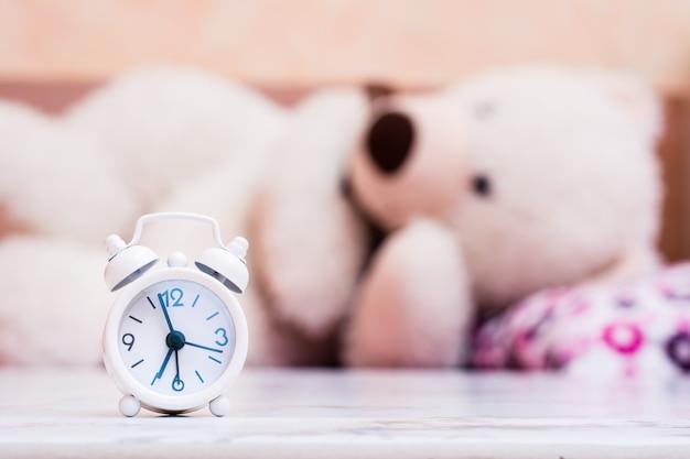 Weißer wecker steht auf dem tisch Premium Fotos