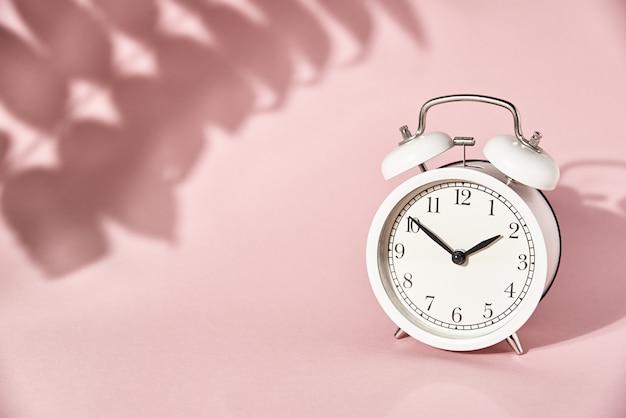 Weißer wecker und hinterlässt schatten auf pastellrosa hintergrund. kreatives minimal-time-konzept Premium Fotos