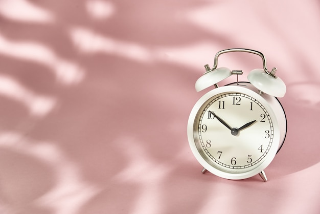 Weißer wecker und hinterlässt schatten auf pastellrosa. kreatives minimal-time-konzept Premium Fotos
