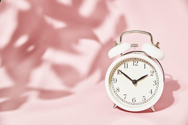 Weißer wecker und hinterlässt schatten auf pastellrosa. Premium Fotos