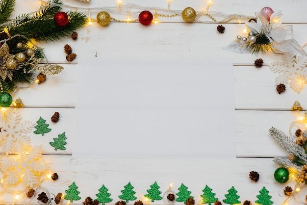 Weißer weihnachtshintergrund verziert mit festlichem dekor, laternen, schneeflocken und weihnachtsbaumzweigen Premium Fotos