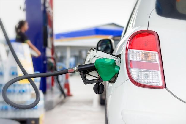 Weißes autotankungsbenzin durch selbstausgabendüse an der tankstelle mit warmem sonnenlicht Premium Fotos