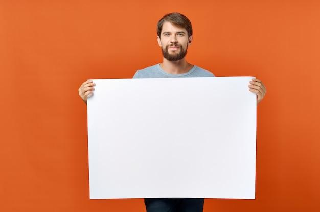 Weißes blatt papierwerbung mann im hintergrund orange hintergrund modell modell poster. hochwertiges foto Premium Fotos
