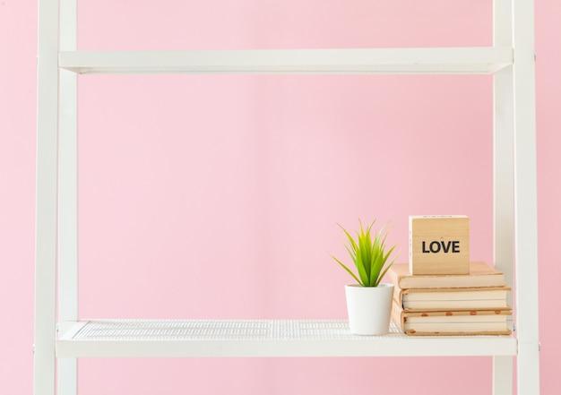 Weißes bücherregal mit büchern und anlage gegen rosa wand Premium Fotos