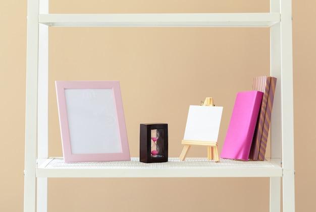 Weißes bücherregal mit büchern und briefpapier gegen beige wand Premium Fotos