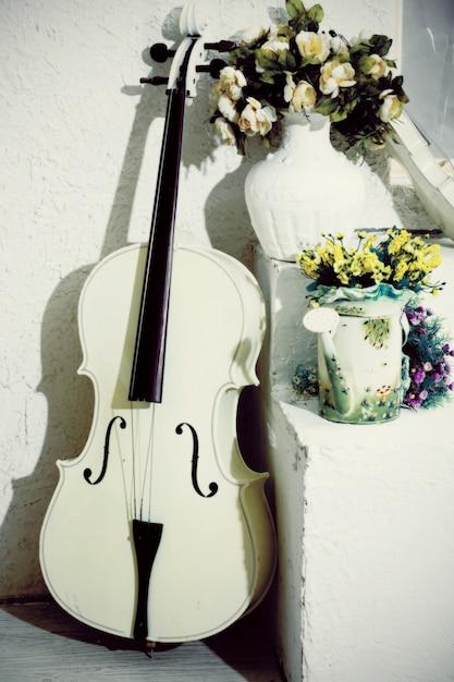 Weißes cello mit blumen im reinraum Premium Fotos