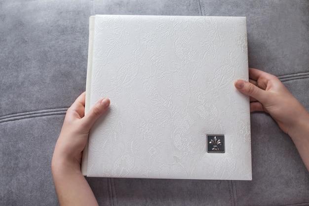 Weißes fotobuch mit lederbezug. frauenhände, die ein fotobuch halten. stilvolles hochzeits- oder familienfotoalbum Premium Fotos