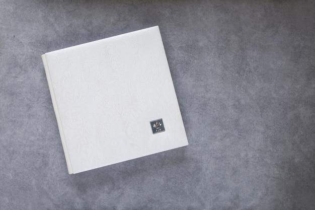Weißes fotobuch mit lederbezug. stilvolles hochzeits- oder familienfotoalbum. schöner notizblock oder fotobuch mit eleganter durchbrochener prägung auf grauem hintergrund. speicherplatz kopieren Premium Fotos
