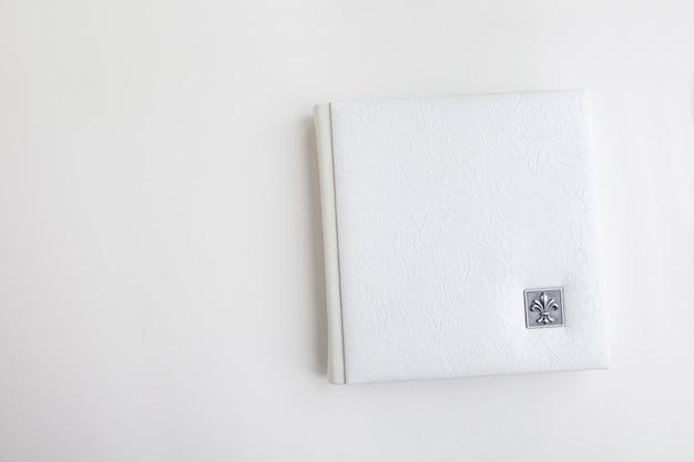 Weißes fotobuch mit lederbezug. stilvolles hochzeitsfotoalbum. familienfotoalbum auf dem weißen tisch. schöner notizblock oder fotobuch mit eleganter durchbrochener prägung auf weißem hintergrund. Premium Fotos