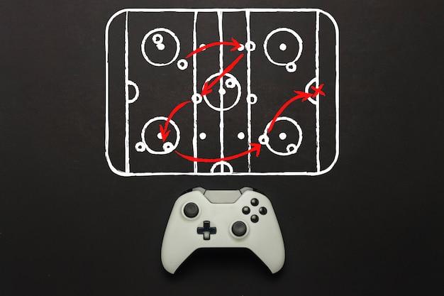 Weißes gamepad auf schwarzem hintergrund. hockeyplatz schema hinzugefügt. taktik des spiels. konzept hockeyspiel auf der konsole, computerspiele. flache lage, draufsicht. Premium Fotos