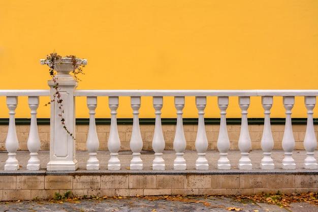 Weißes geländer mit säulen und einer vase für blumen. die wand ist mit gelber farbe bemalt. Premium Fotos