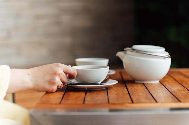 Weißes geschirr, großer kessel, tasse, schüssel, porzellanlöffel auf einem grauen gradientenhintergrund Premium Fotos