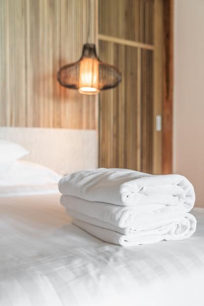 Weißes handtuch auf dem bett Premium Fotos