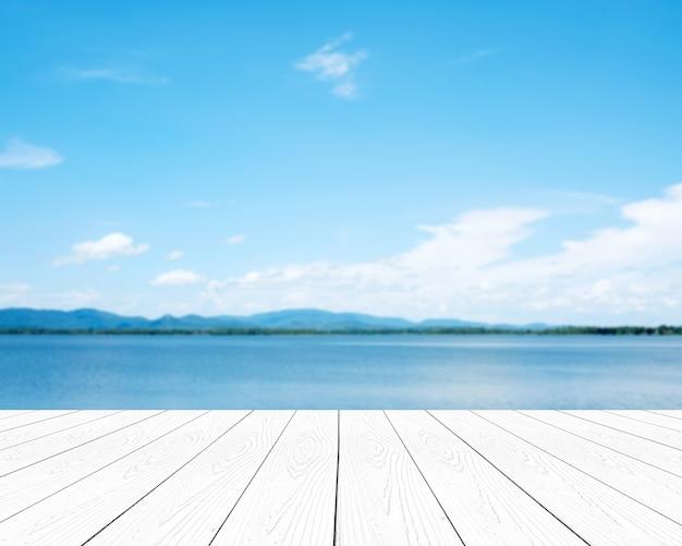 Weißes holz der leeren perspektive über blauem meer- und himmelhintergrund der unschärfe Premium Fotos