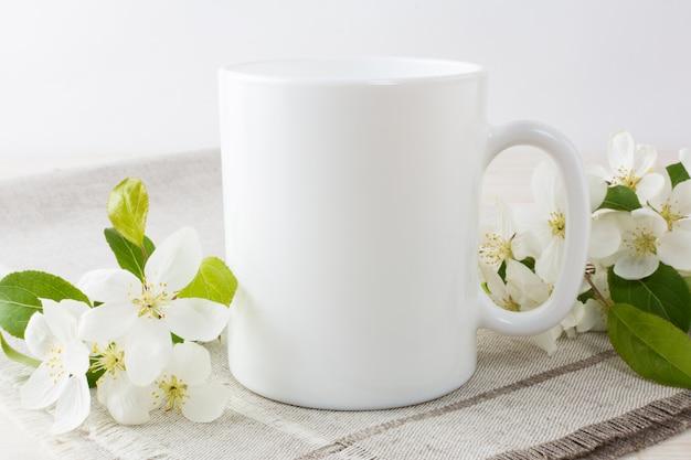 Weißes kaffeetassemodell mit apfelblüte Premium Fotos