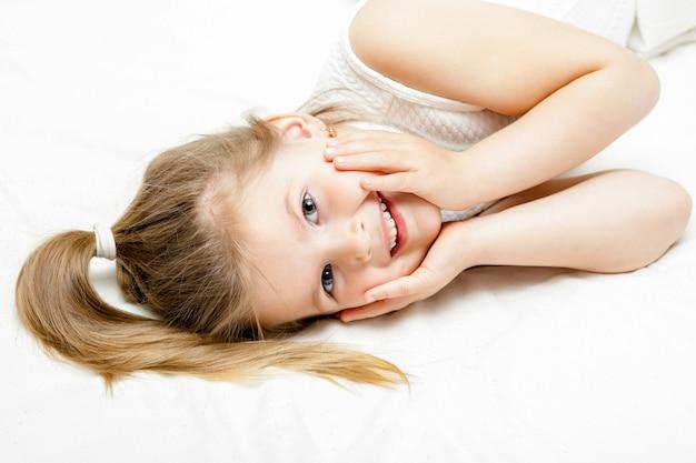 Weißes kleid des recht kleinen blonden mädchensommers, das auf dem boden liegt und an der kamera auf weiß lächelt Premium Fotos