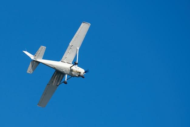 Weißes kleines flugzeug, unten verrostet, in san diego am himmel drehend Kostenlose Fotos