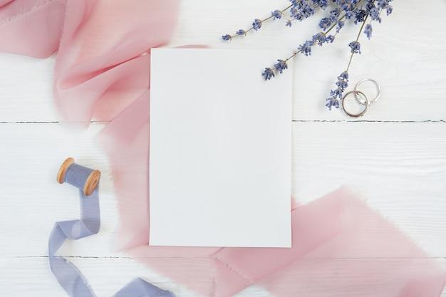 Weißes leeres kartenband mit zwei eheringen Premium Fotos