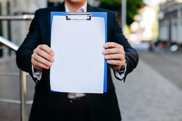 Weißes leeres leeres modell der nahaufnahme des papierblattes in den männlichen händen - kopieren sie raum Premium Fotos